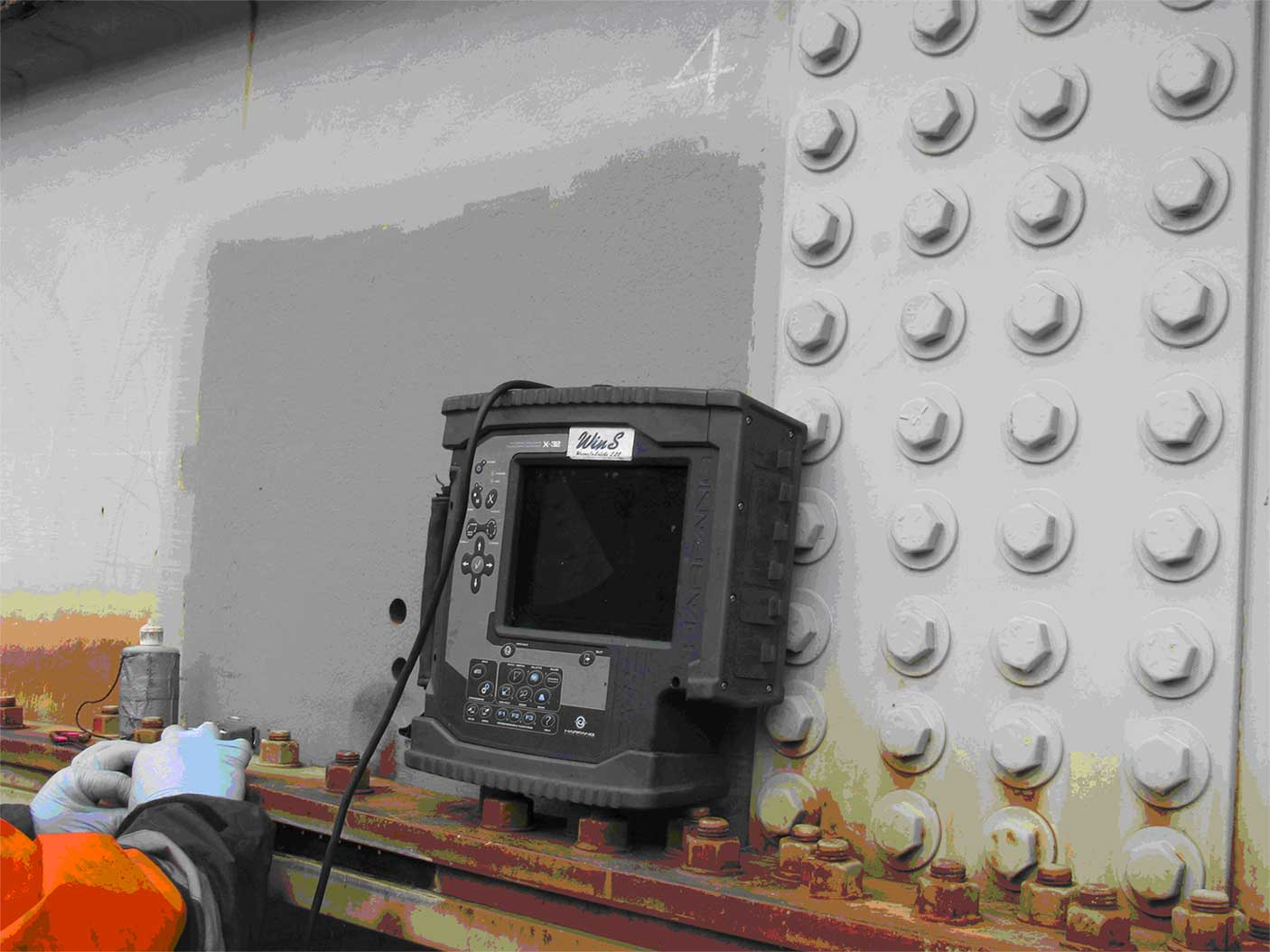 Inspector using Ultrasonic testing during a bridge inspection.