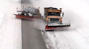 Combination truck pulling a tow-plow