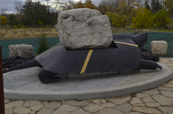 Sculpture of a Turtle made from steel with a large stone resting on its back