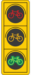 Diagram of a bicycle traffic signal: The diagram shows a bicycle traffic signal. There are three dark circular lenses arranged vertically with a coloured bicycle symbol on each lens. The top lens has a red bicycle symbol, the middle lens has an amber bicycle signal and the lens at the bottom has a green bicycle signal.