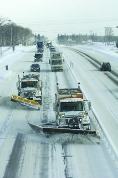 Maintenance vehicles plowing a 2-lane highway