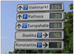 The use of real-time parking displays, such as this one in Germany, can help to maximise existing shared parking resources by informing drivers of the location of available spaces within a structure or district.