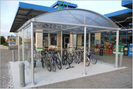 Sheltered bike facilities located in highly visible locations, such as this example in Oakville, help discourage vandalism and theft. The use of closed rings provides two points of contact for parked bicycles. This provides greater stability and makes it easier to lock the bike.