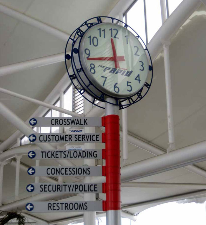 A clock and highly visible directional signage located at a key decision point at this station in Grand Rapids, MI, assists travellers in making quick decisions when travelling through the station.