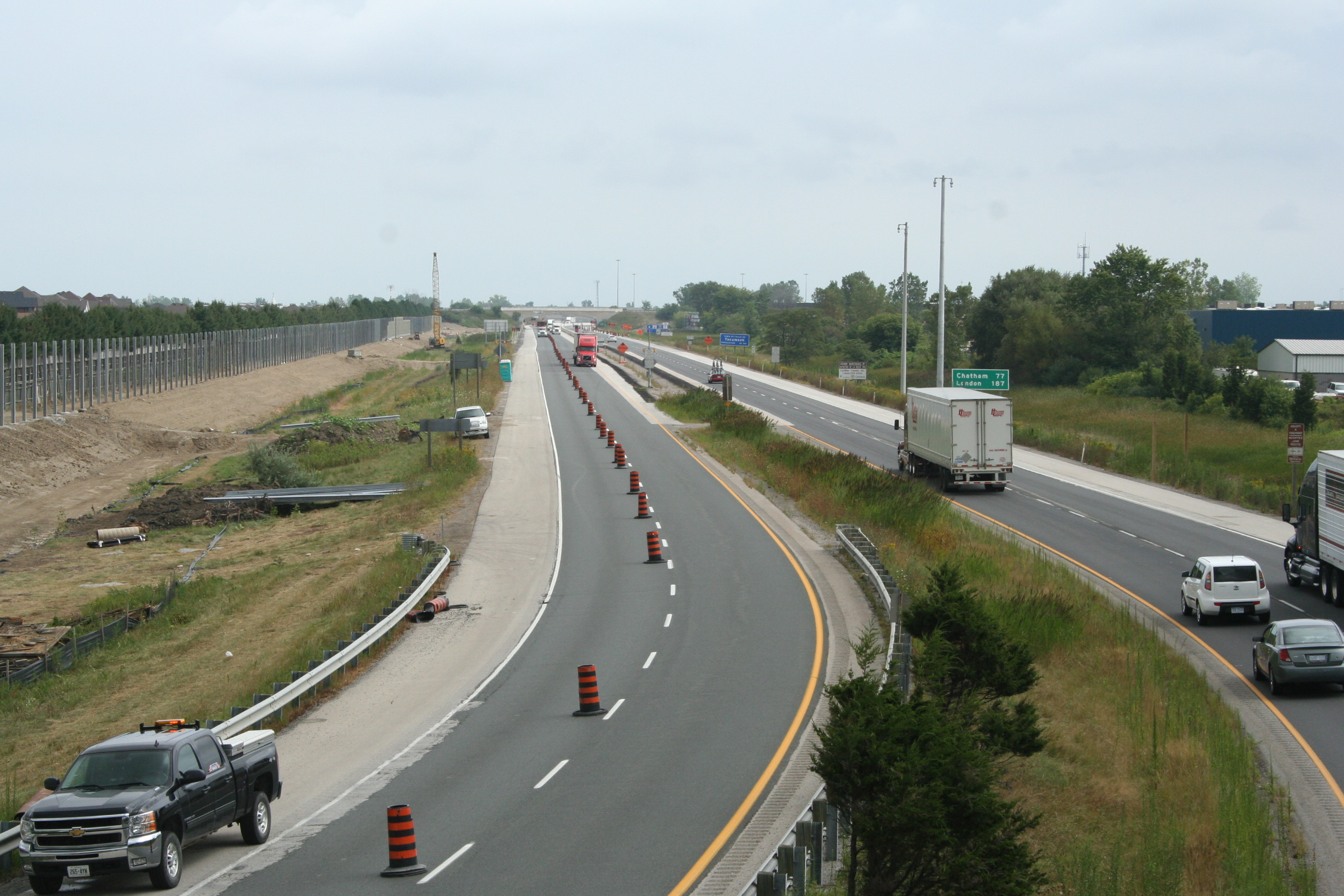 "The left side of this photo shows noise barrier poles being ""planted"" by the highway at Tecumseh on Highway 401, in preparation for noise barrier installation."