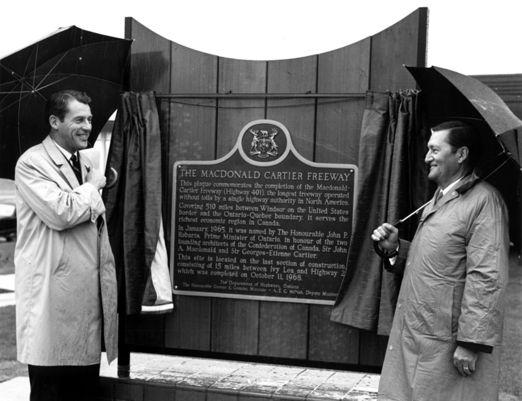 Officials standing next to a plaque that commemorates the completion of Highway 401 (Macdonald-Cartier Freeway), 1968-1969. <br> Image from MTO's collection.