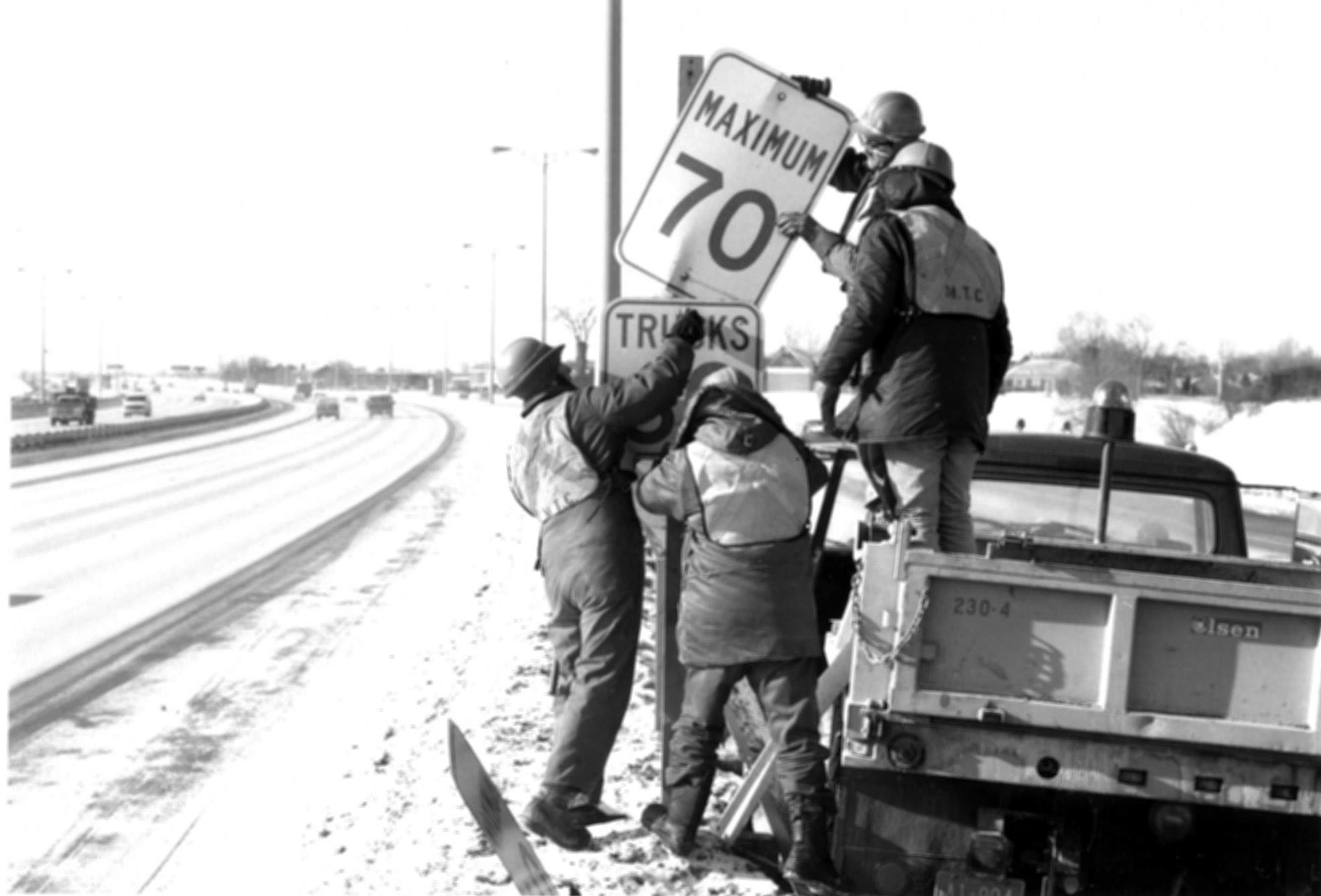 Workers removing speed signs (replaced with reduced speeds) on Highway 401, 1976. <br> Image from MTO's collection.